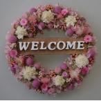 玄関ドアに、白とピンクのお花のかわいらしい色合いのウェルカムリース