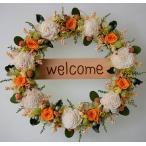 玄関ドアに、オレンジ色のバラと白のソーラーフラワー、プリザーブドフラワーのウェルカムリース