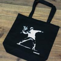 シックな雰囲気にも使い勝手の良いブラックカラーのキャンバストートバッグ。   社会を風刺する謎の覆面...