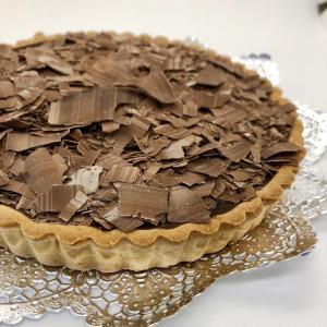 しっとり、こくのあるチョコレート生地を、グラッサージュでおおい、さらに削ったチョコレートをのせて仕上...