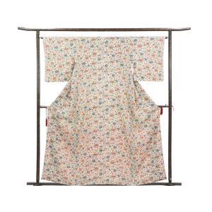 正絹の薄ベージュ地の袷小紋着物です。沖縄の伝統工芸の紅型に似たような意匠で細かい花柄が総柄で染められ...
