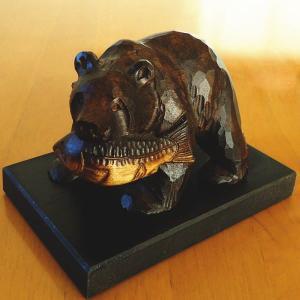 木製の木彫りの鮭を喰わえた熊の置物です。  手作りによる作品のため、写真とは異なる場合がございます。...