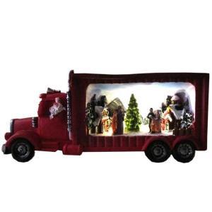 赤いトラックの中に、クリスマスシーズンの街並み。レンガの家々に積もる雪が印象的です。讃美歌をうたう...