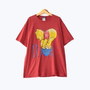 くまのプーさんのプリント半袖Tシャツです。 プーさんが大好きなはちみつ瓶の上に乗っかって蓋を外そうと...