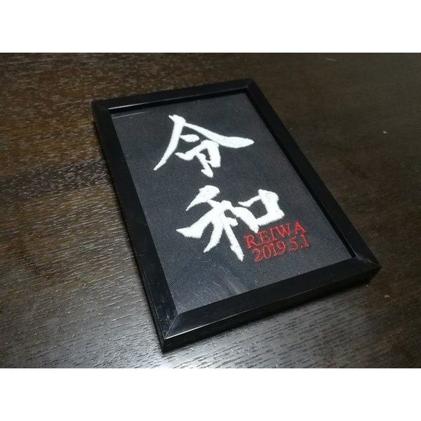 令和元年お祝いグッズ REIWA/Lサイズ暗闇で光る令和デザイン刺繍年月日付ブラックフレーム入り/蓄光糸ver